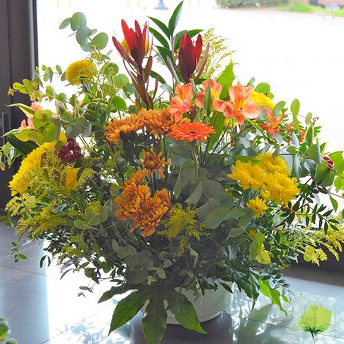 Composición floral redonda en color amarillo, rojo y naranja